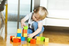 Kid playing toy blocks inside his house Stock Photos