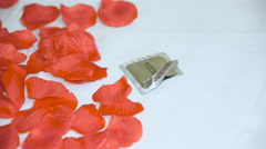 Someone throws the exposed empty packaging of a condom in rose petals on the bed Stock Footage