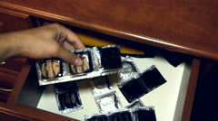 Someone opens a drawer and pulls himself two of the many condom, close-up Stock Footage