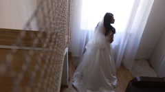 Stylish luxury gorgeous brunette bride posing near window on the background Stock Footage