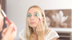 Young woman doing makeup in front of a mirror, full face, blurred background. Stock Footage