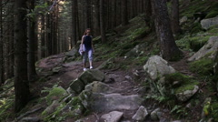 Woman traveler is walking through the mountains and forests Stock Footage