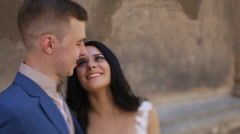 Close-up of charming bride and groom looking at each other on ancient street Stock Footage