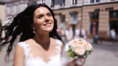 Smiling brunette bride with bright face looking up walking on the street in a Stock Footage