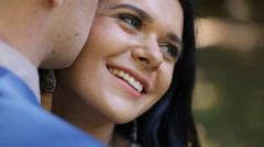 Close-up beautiful brunette bride smiling while groom whispering compliments to Stock Footage