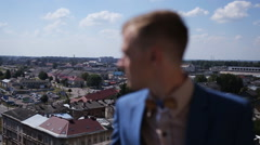 Happy handsome groom in blue suit looking at old european architecture Stock Footage