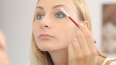 Young woman doing makeup in front of a mirror, full face, blurred background. - stock footage