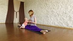 The young blonde girl practicing yoga with her child in the hall. 4K - stock footage