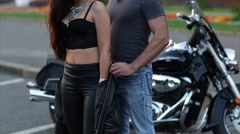 A Man Helps to Wear a Jacket to His Girlfriend Standing Near the Motorcycle Stock Footage