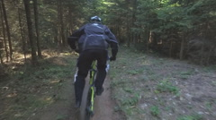 Man on mountain bike riding bike in the forest and performing tricks and jumps Stock Footage