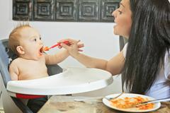 Mother feeding hungry six month old baby solid food Stock Photos