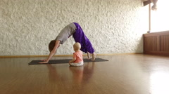 The young blonde girl practicing yoga with her child in the hall. 4K Stock Footage