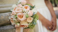 Pink and white wedding bouquet of roses and hands of the bride with wedding ring - stock footage