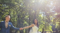 Happy bride walking holding a dress in one arm and groom's hand in another Stock Footage
