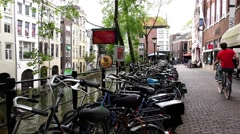 People ride bikes along the Oudegracht old canal in center of Utrecht Stock Footage