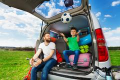 Father playing ball with son sitting in car boot Stock Photos