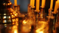 Group of dimly lit, burning white candles create mood, ambiance, close up, black Stock Footage
