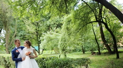 Elegant bride and groom posing together outdoors on a wedding day, embracing Stock Footage