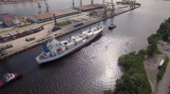 Two boats towing a container ship in channel, aerial view Stock Footage