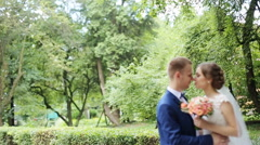 Young wedding couple enjoying romantic moments standing face-to-face outside in Stock Footage