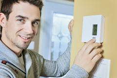 man set the thermostat at house - stock photo