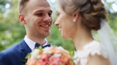 Happy smiling bride and groom on their wedding day posing with bridal bouquet Stock Footage