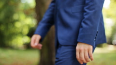 Close up side view of groom in blue suit walking on nature at sunny day Stock Footage