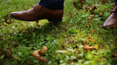Male feet in blue suit and brown shoes walking on green park grass with autumnal Stock Footage