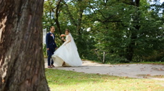 Happy bride and groom walking and holding hands in the park Stock Footage