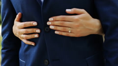 Close up portrait of bride hugging her groom from behind, female hands on man's Stock Footage