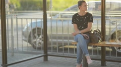 Beautiful young Woman waiting public transportation at urban setting station and Stock Footage