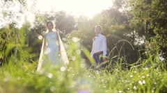 Bride and groom standing together holding hands on a gorgeous blooming summer Stock Footage