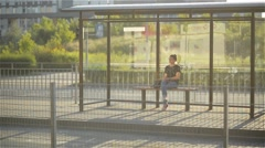 Beautiful young Woman waiting public transportation at urban setting station Stock Footage