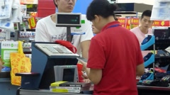 WAL-MART supermarket cashier, customers in the checkout Stock Footage