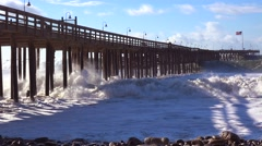 Huge waves crash on a California beach and pier during a very large storm event. Stock Footage
