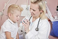 Medical doctor applying oxygen treatment on a little boy with as - stock photo