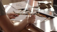 Male artist's hand sketching sofa with a pencil on a light day Stock Footage