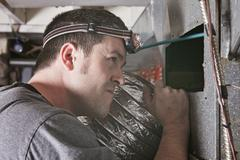 ventilation cleaner man at work with tool - stock photo