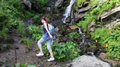 Hiker woman with backpack walking on a forest trail in the mountains on the Stock Footage