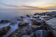 Empty sea and rocks During the sunset with Silky Sea Stock Photos