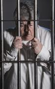 Female Prisoner in Jail holding bars - stock photo