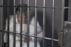 Female Prisoner in Jail -crying behind bars - stock photo