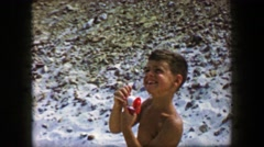 1959: Boy flying kite string reel controlling closeup crank beach activity. CAPE Stock Footage