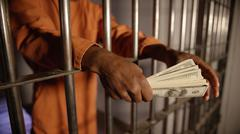 Man in Jail holding a stack of american money - stock photo