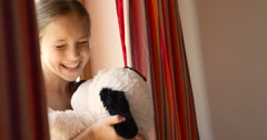 Cute beautiful little girl sitting on the windowsill with red-curtains and Stock Footage