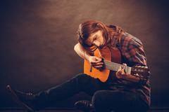 Hippie with wooden guitar. - stock photo