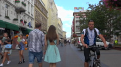 Warsaw centrum, walkers and cyclists in a pedestrian street - sunny summer day Stock Footage