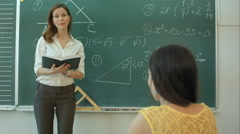 Teacher or docent or educator giving while lesson in front of a blackboard or Stock Footage