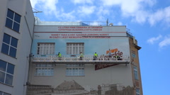 Workers on scaffolding painting the frontage of a tall building - Zoom in Stock Footage