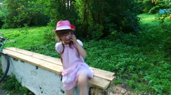 Little girl talking on a mobile phone. She moves through the park. Stock Footage